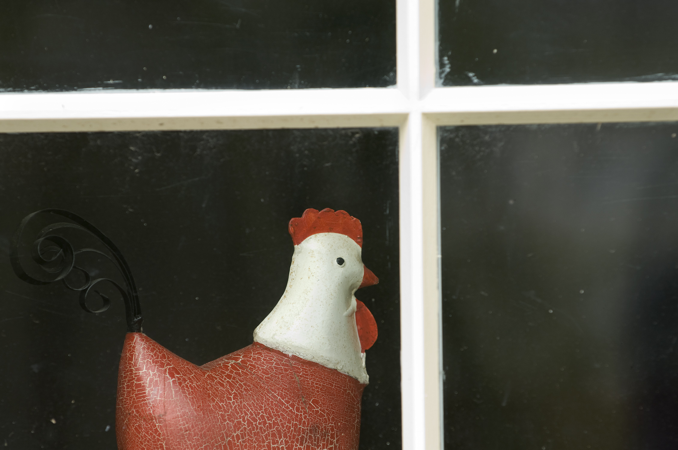 A window showing a ceramic Chicken ornament